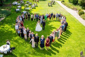 Gruppenfoto in Herzform mit dem Hochzeitspaar in der Mitte
