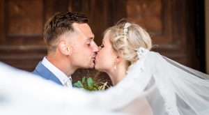 Braut mit langem Schleier küssend